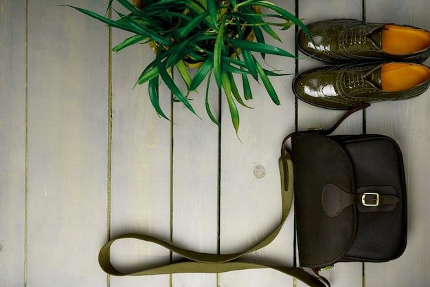 緑の漆塗りのオックスフォードシューズと植木鉢の近くの木製の背景にクロスボディバッグ。上面図。閉じる。コピースペース