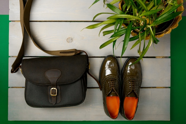 Green lacquered oxford shoes and crossbody bag on wooden