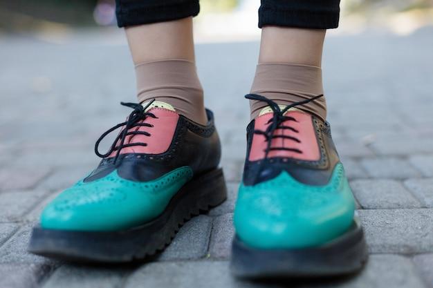 Зеленые лакированные оксфорды. вид сверху. закройте вверх. хипстерская женщина носит модную обувь лоферы с кисточками