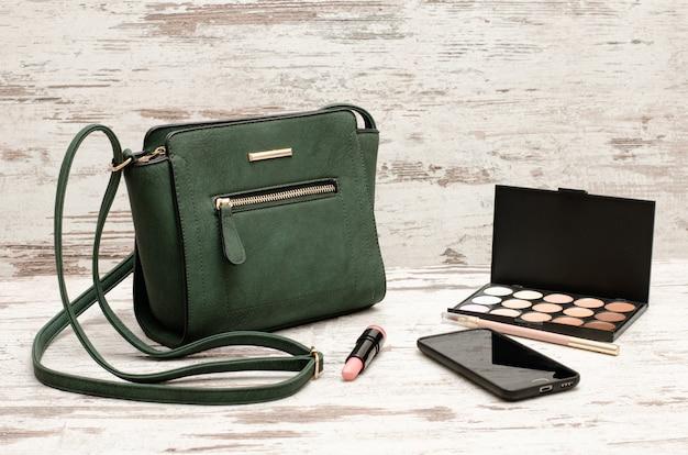 緑の女性のハンドバッグ、電話、アイシャドウパレット、木製の背景に口紅