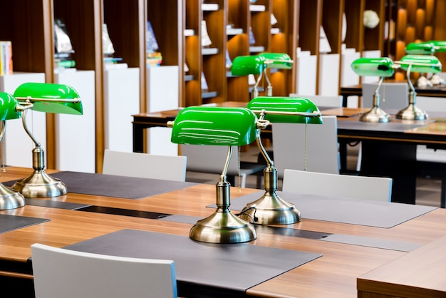Green lamps on table in library
