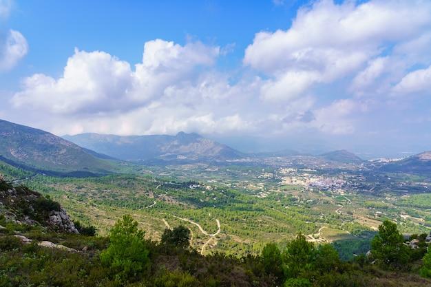 白い家の小さな村と谷の緑の風景のパノラマ。アリカンテスペイン。