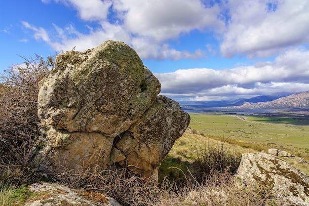 Зеленый пейзаж с большими скалами, озером и горами на заднем плане и белыми облаками на голубом небе. навасеррада мадрид. европа.