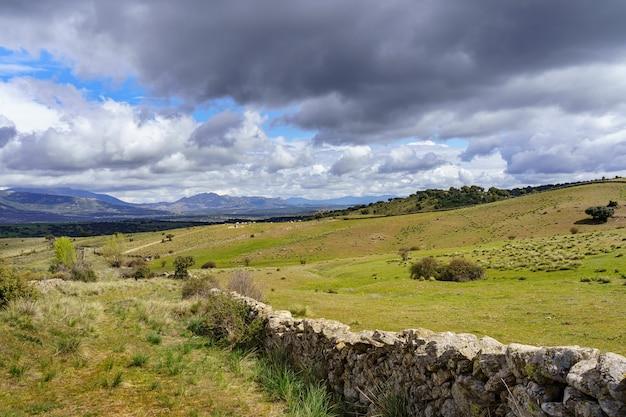 劇的な空と草の牧草地を分離する天然石の柵のある緑の風景。マドリッド。