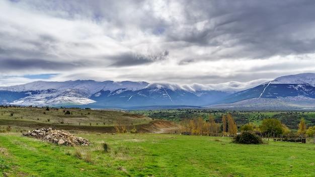 ソモシエラマドリードの雪山と劇的な空と緑の風景。ヨーロッパ。