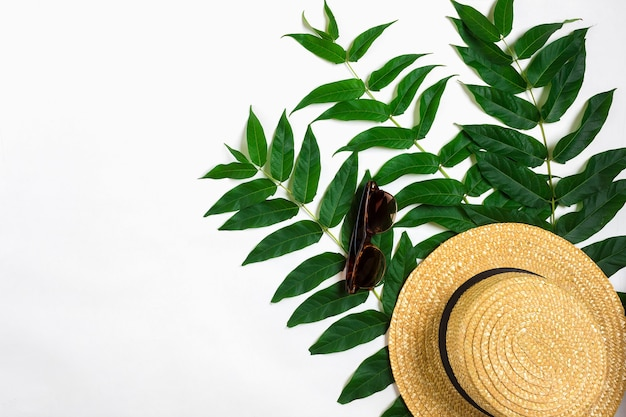 Green leaf branches and straw haton white background flat lay top view