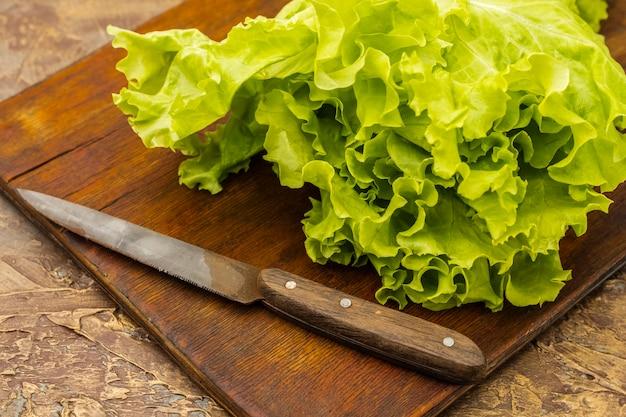 古いまな板の上の緑の葉レタス。ダイエット食品の調理