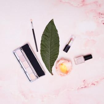 Green leaf; lipstick; nail varnish; petals; makeup brush and eyeshadow palette on pink backdrop