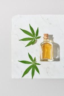 影付きの明るい灰色の大理石のテーブル、コピースペースに有機成分から抽出されたcbdオイルのボトルが付いた医療大麻植物の緑の葉。医療目的での大麻の使用。