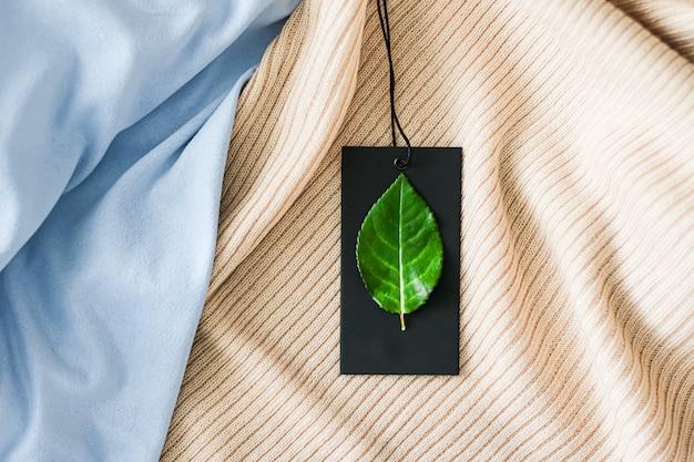 Зеленый лист на бирке одежды и фоне органической ткани устойчивая мода и концепция бренда