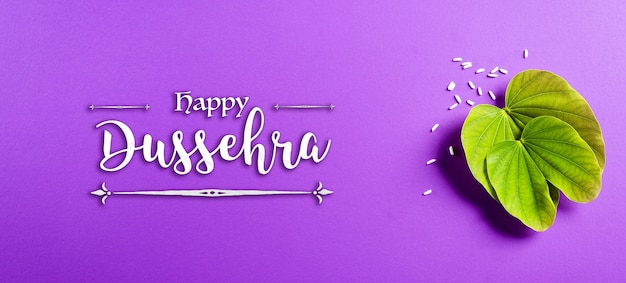 Green leaf and rice on purple pastel background dussehra banner