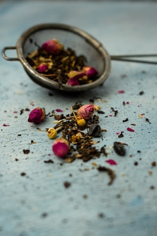 Green leaf tea for brewing in a sieve with dried rose buds