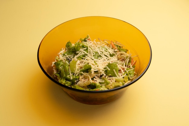 Green leafy salad seasoned with grated parmesan cheese covering in a yellow table