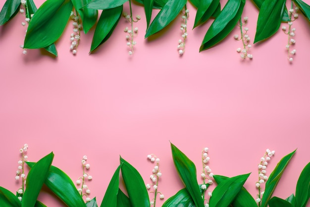 緑の葉と谷のリリーの小さな花束は、コピースペースフラットと花のボーダーとして横たわっていました...