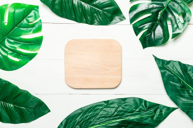 Green leaves around blank wooden board