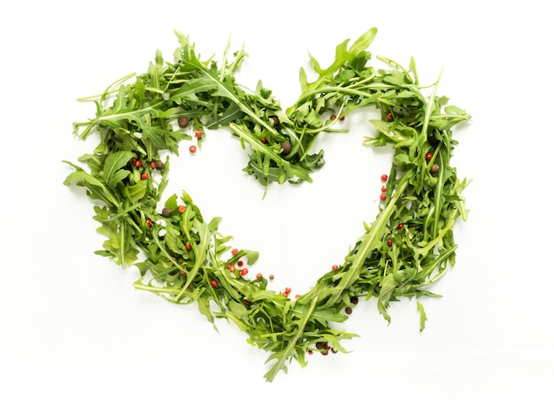 Green leaves of arugula laid out in the shape of heart on white background.
