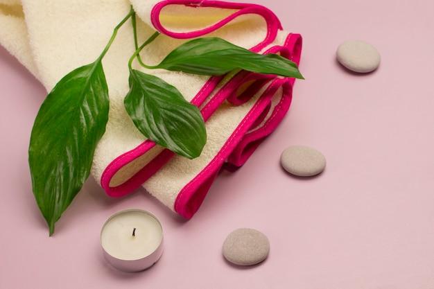 緑の葉、キャンドル、スパストーン、ピンクのボーダーのタオル。 spaリラクゼーションコンセプト。ピンクの背景。上面図