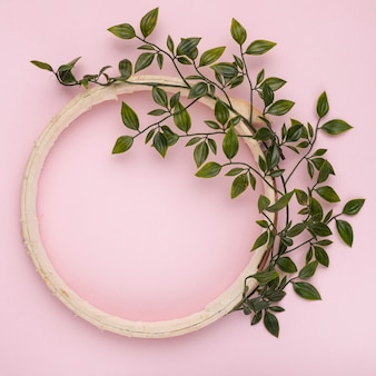 Green leaves decorated on wooden empty circle frame against pink backdrop