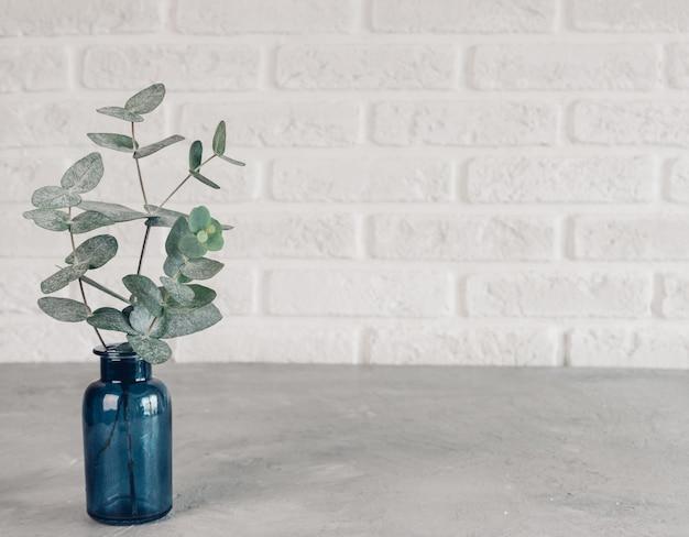 Зеленые листья эвкалипта в синей вазе на фоне белой кирпичной стены в скандинавском стиле минимализма.
