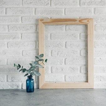 Зеленые листья эвкалипта в синей вазе и деревянной фоторамке на фоне белой кирпичной стены минимализм в скандинавском стиле.