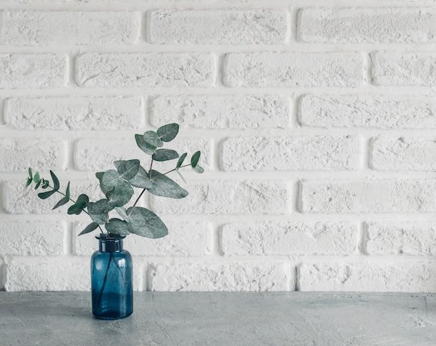 Зеленые листья эвкалипта в синей вазе на белой кирпичной стене