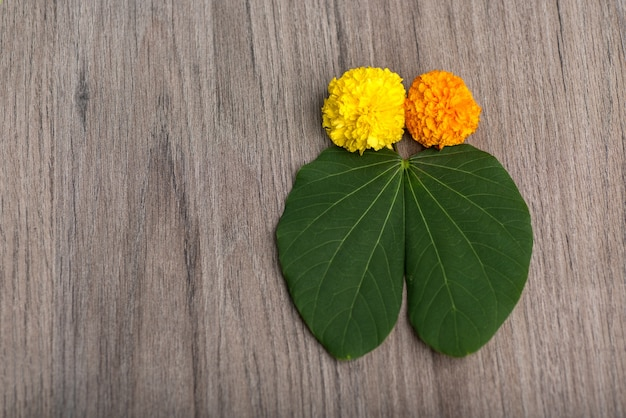 Green leaves and marigold flowers on a wooden background