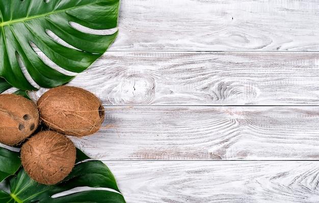 緑は白い木製の背景の上面図にココナッツとモンステラを残します。テキスト、バナーのコピースペース。