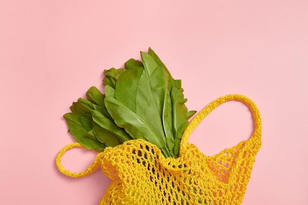 Зеленые листья щавеля в желтом мешок строки на розовом фоне. ноль отходов. хлопок.
