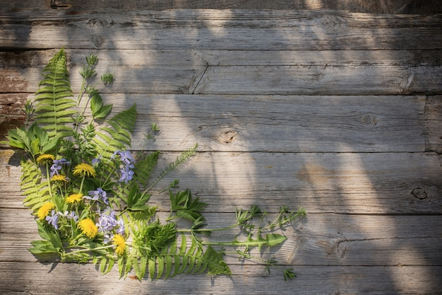Green leaves on old wooden background