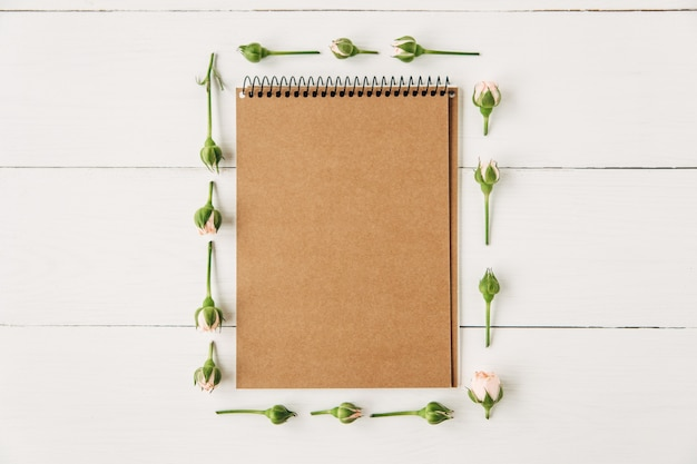 Green leaves and pink roses with brown notebook in the middle on white wooden boards background