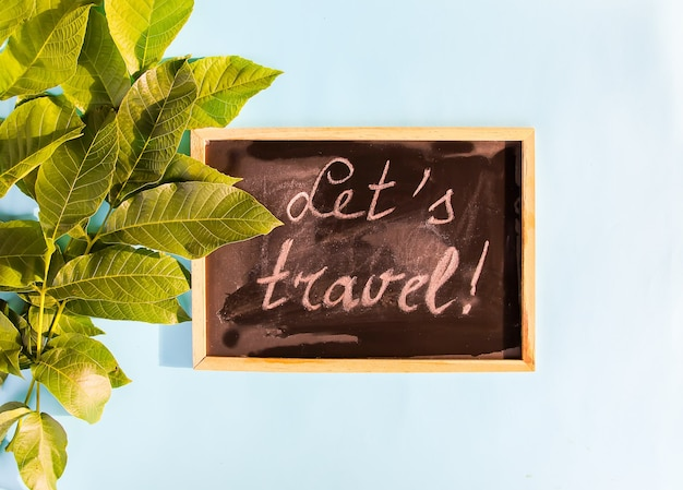 Green leaves in sunlight on soft blue pastel background and chalkboard with words let's travel!