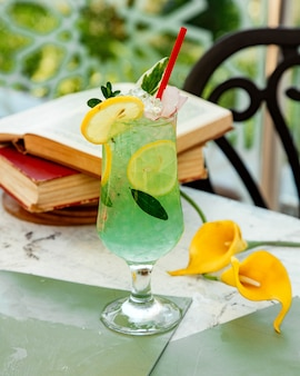 Green lemon cocktail with ice and lemon slices
