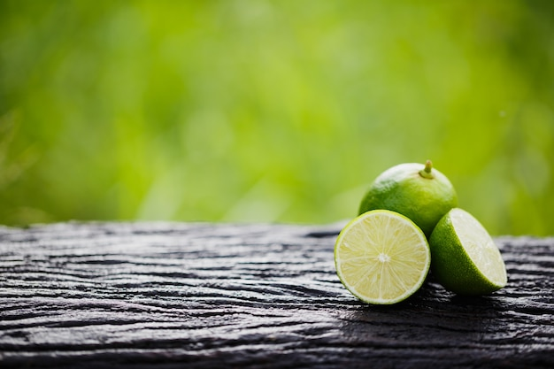 Green lemon sliced on wood with green background