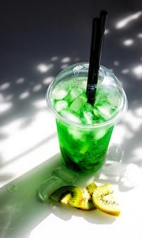 얼음과 키위 조각이 있는 녹색 레모네이드. 플라스틱 컵이 탁자 위에 있습니다.