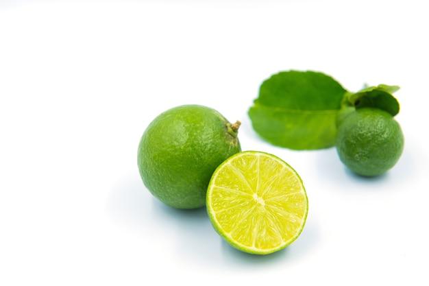 Зеленые лимоны на белом