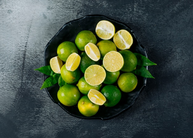 Green lemons in a plate with slices top view on a black textured background