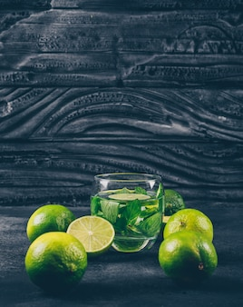 Green lemons in a water glass with slices side view on a black textured background space for text