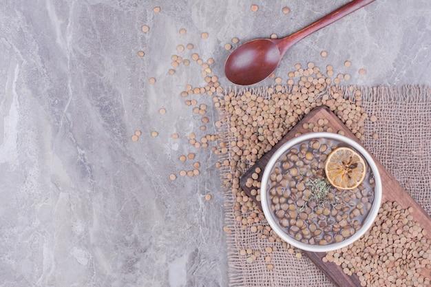 木の板の白いボウルにグリーンレンズ豆のスープ