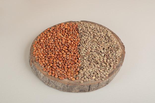 木の板に緑レンズ豆と茶色の豆。