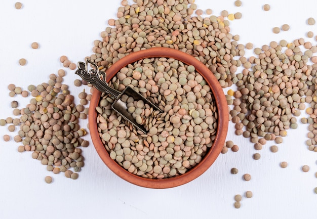 Green lentils in a brown bowl and iron spice spoon