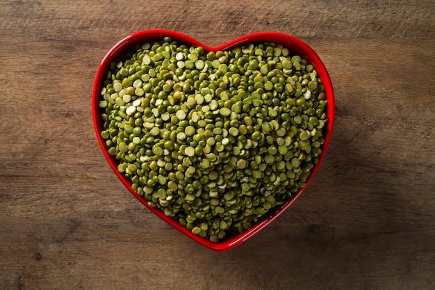 나무 바탕에 하트 냄비 안에 녹색 렌즈 콩. 콩과 식물의 식용 생 맥박.