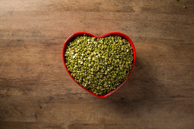 Green lentils inside a heart pot on wood background. edible raw pulses of the legume family.