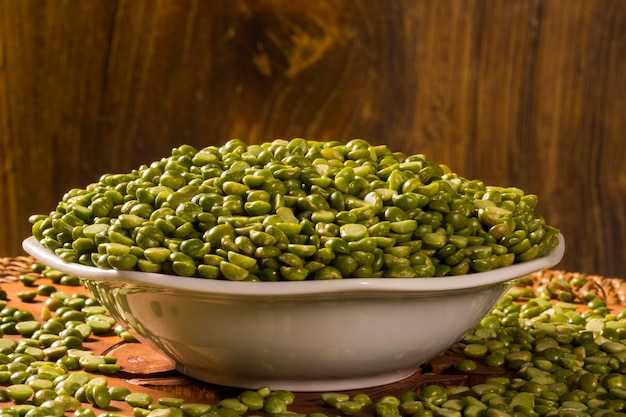 Green lentils inside a white pot on wood background. edible raw pulses of the legume family.