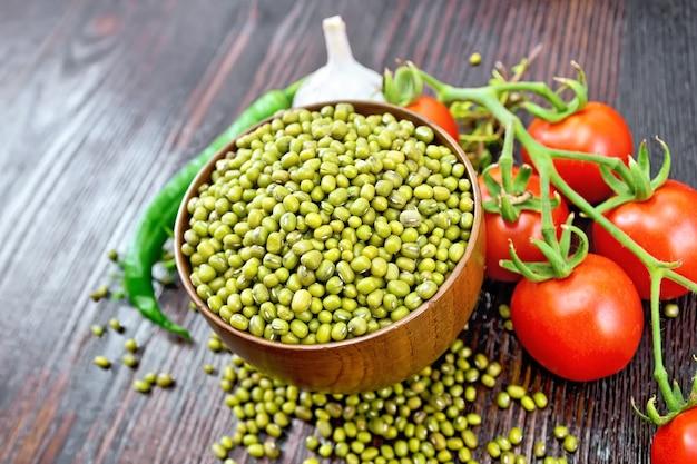 ボウルに緑レンズ豆、唐辛子、ニンニク、木の板の背景に赤いトマト