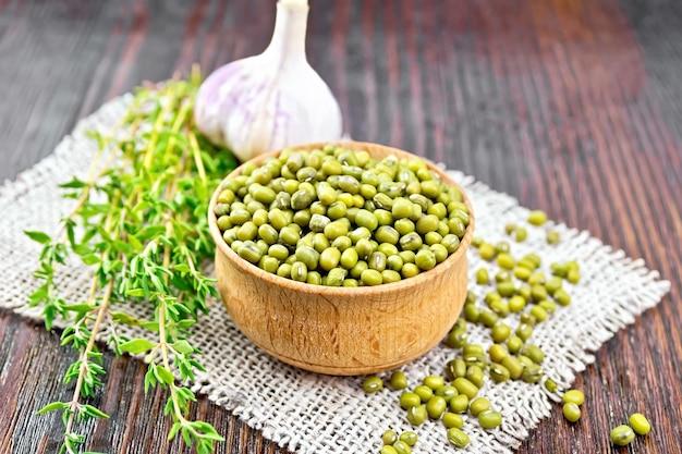緑のレンズ豆は、黄麻布のナプキンにタイムとニンニクを入れた木製のボウルに入れ、唐辛子を暗い板に当てます