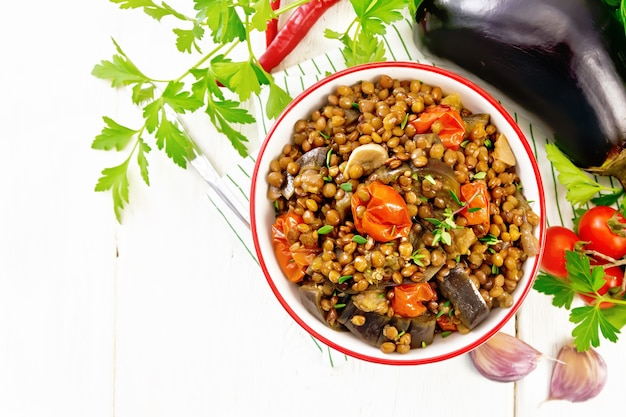 Green lentils stewed with eggplant, tomatoes, garlic and spices in a bowl on a kitchen towel, parsley on wooden board background from above