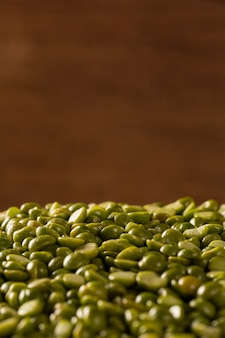 Green lentils in wooden bowl on wood background. edible raw pulses of the legume family.
