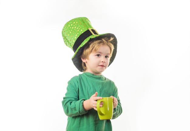 Зеленый лепрекон. ребенок в зеленой шляпе держит чашку. зеленая шляпа с клевером. день святого патрика. традиции дня святого патрика. день святого патрика. зеленый цилиндр. лепрекон. распродажа. скидка. реклама.