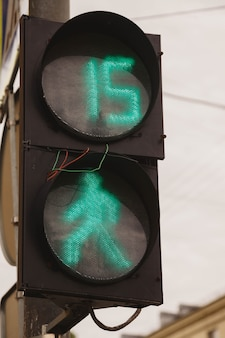 На светофоре горят зеленый свет и пешеход, провода торчат. пешеходный переход в городе. номер 15 на светофоре дает понять, что пешеходы переходят дорогу за пятнадцать секунд.