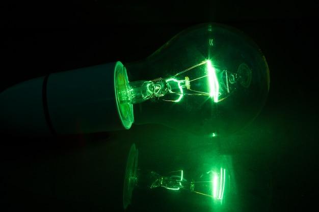Green light bulb turned over on black background